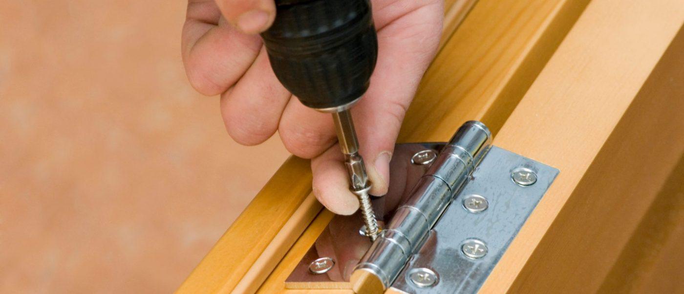 Assemblage of a door. Screwing of screw in hinge of door
